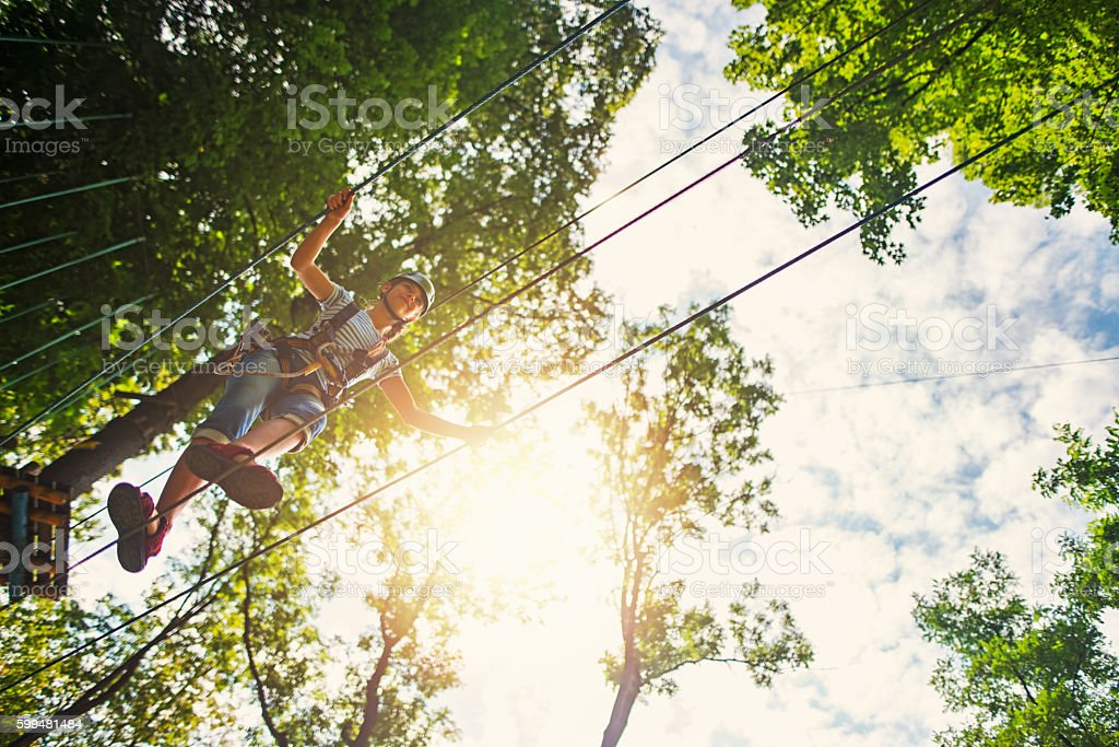 Teenage girl walking on a line in adventure park stock photo