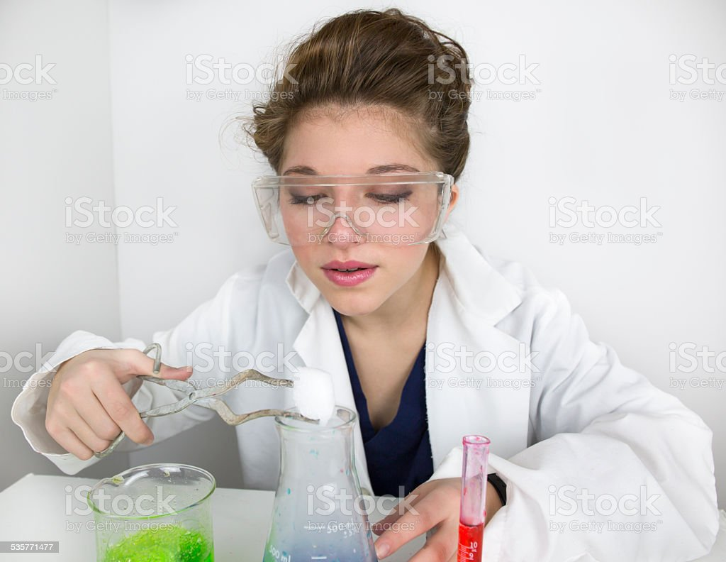Teenage girl wearing goggles doing science experiment stock photo