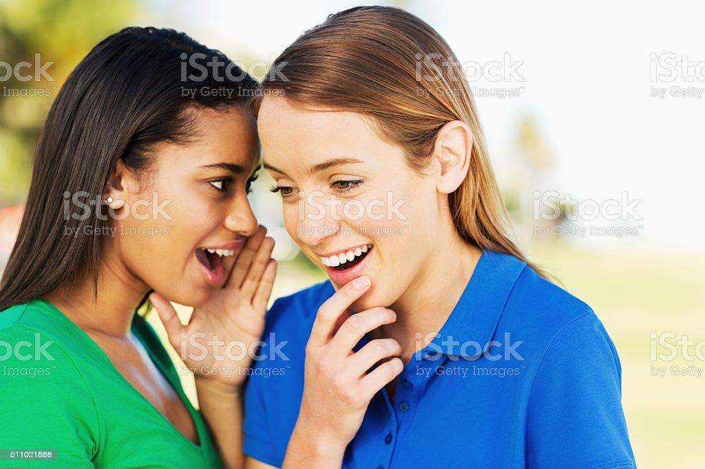 Teenage Girl Whispering Secret In Friend's Ear In Park stock photo