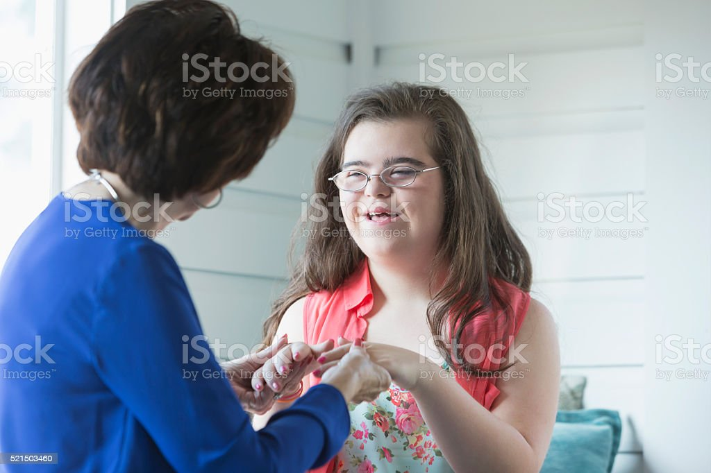 Teenage girl with down syndrome and her grandmother stock photo