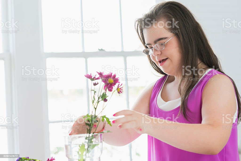 Teenage girl with down syndrome arranging flowers stock photo