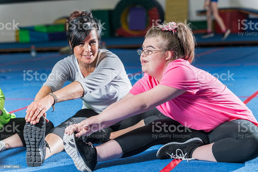 Teenage girl with down syndrome in exercise class stock photo