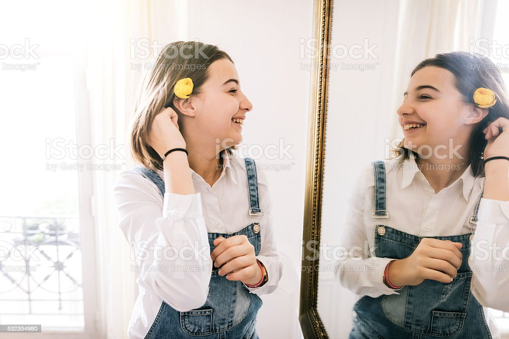 Teenage girl with flower looking into the mirror stock photo