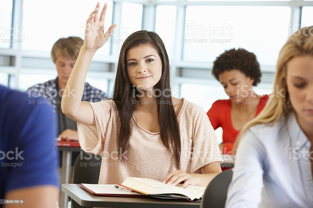 Teenage girl with hand up in class royalty-free stock photo