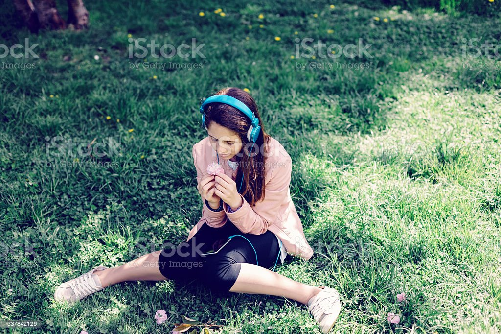 Teenage girl with headphones in the grass stock photo