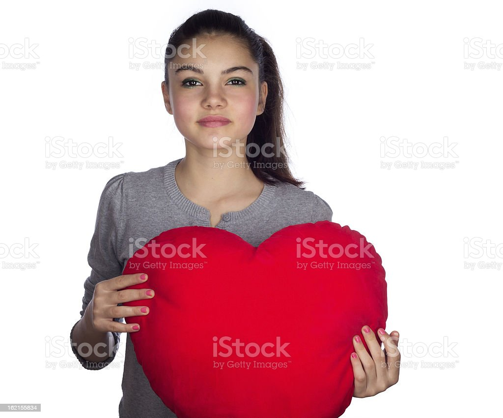 Teenage girl with heart shape pillow royalty-free stock photo