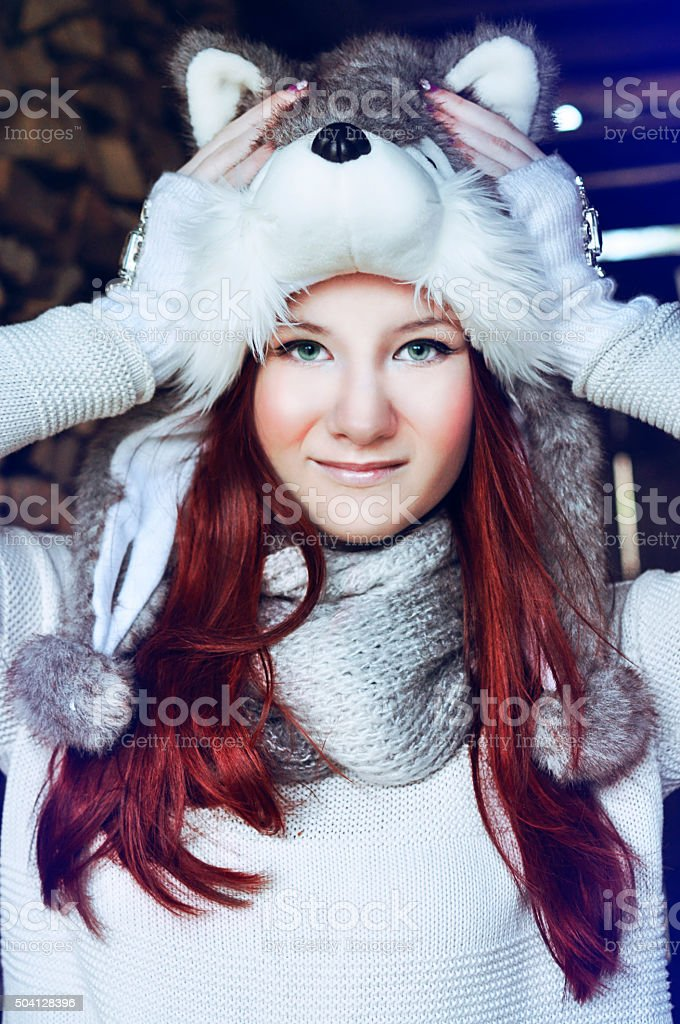 Teenage girl with long red hair wearing a husky hat. stock photo