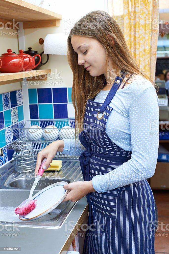 Teenage Girl With Part Time Job Washing Up stock photo