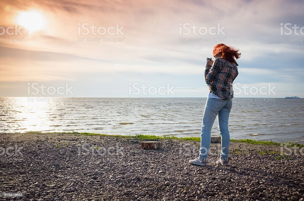 Teenage girl with red hair taking landscape photo stock photo