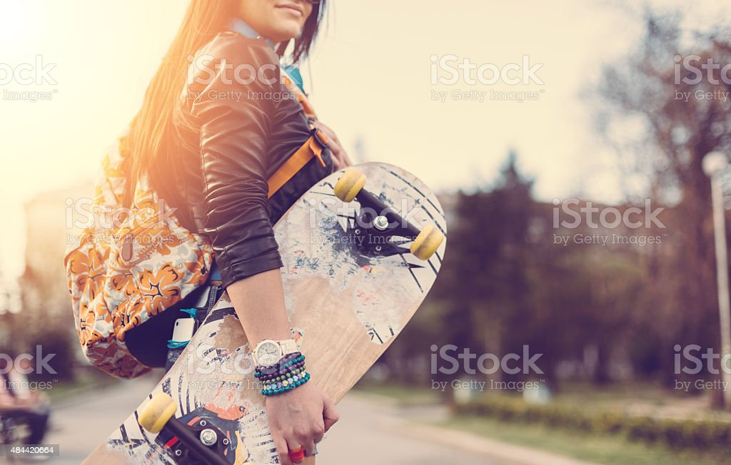 Teenage girl with skateboard in the park stock photo