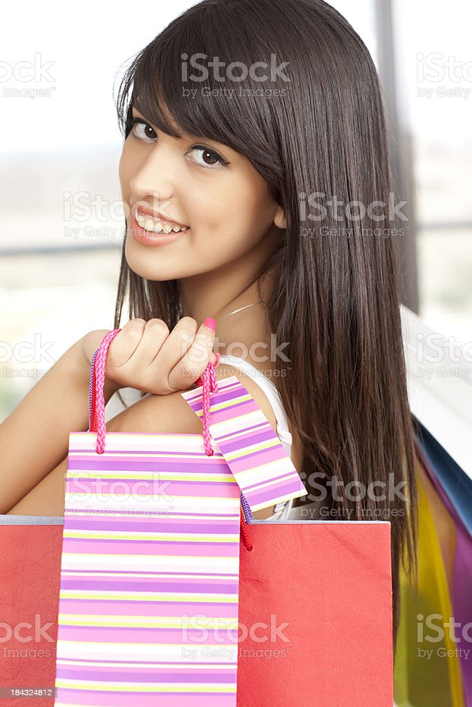 Teenage girl with striped colored shopping bags. royalty-free stock photo