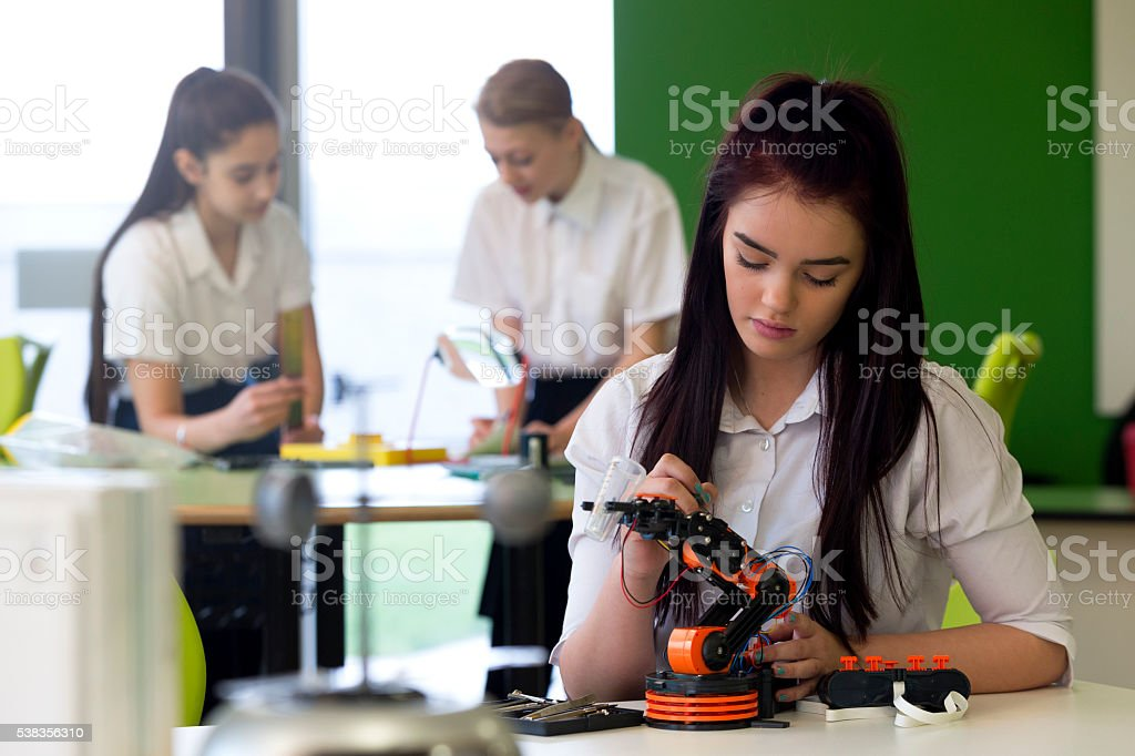 Teenage Girl Working on Robotic Arm stock photo
