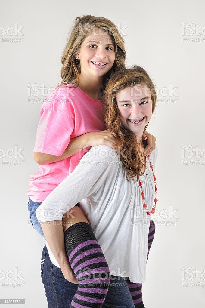 Teenage Girlfriends Having Fun and Smiling, Going Piggyback Riding royalty-free stock photo