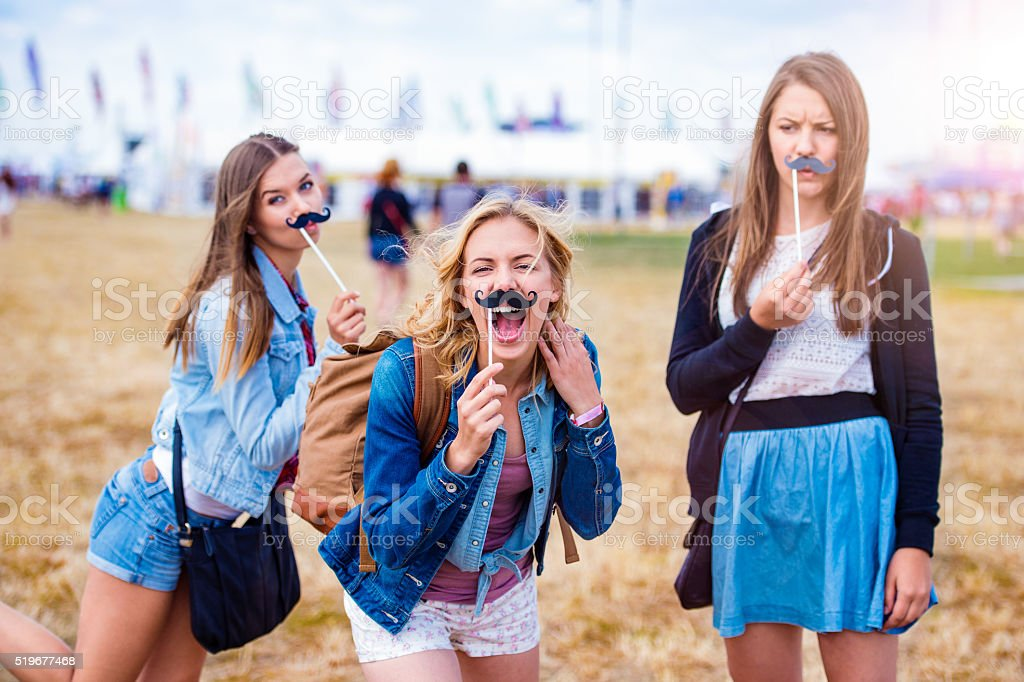 Teenage girls at summer festival with fake mustache stock photo