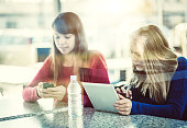 Teenage girls at the coffee bar with digital tablet