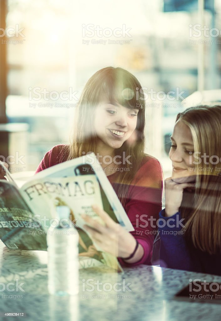 Teenage girls at the coffee bar with reading magazine stock photo