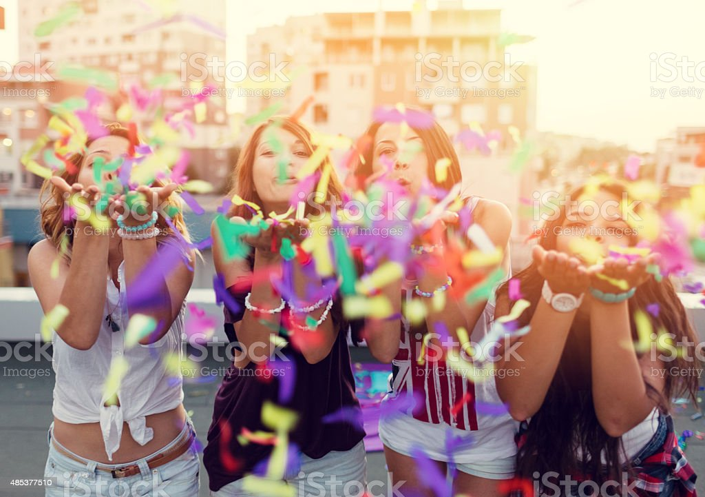 Teenage girls blowing confetti on a rooftop party stock photo