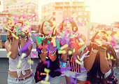 Teenage girls blowing confetti on a rooftop party