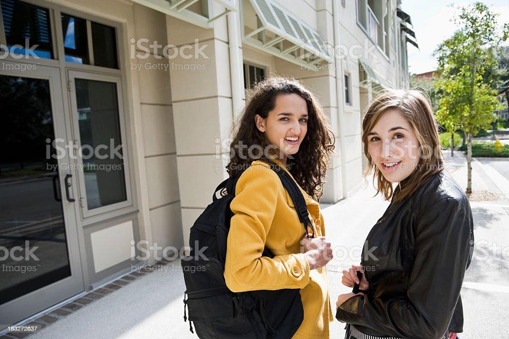 Teenage girls carrying bookbags stock photo