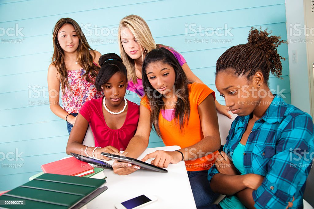 Teenage girls cyber-bully classmate using wireless technology. stock photo