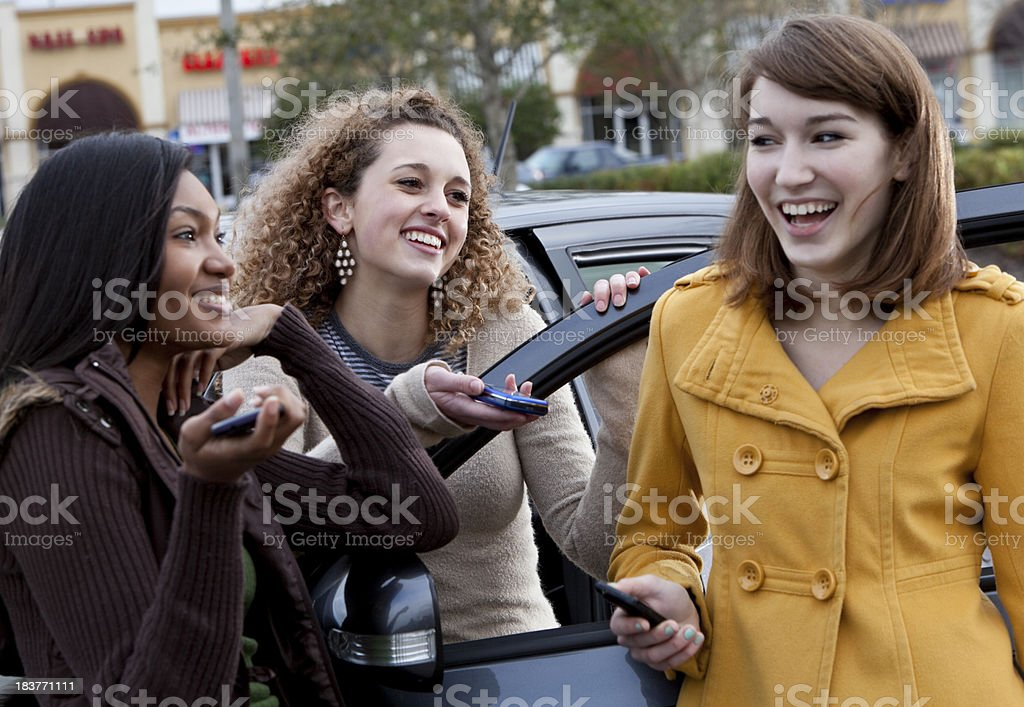 Teenage girls hanging out in parking lot stock photo