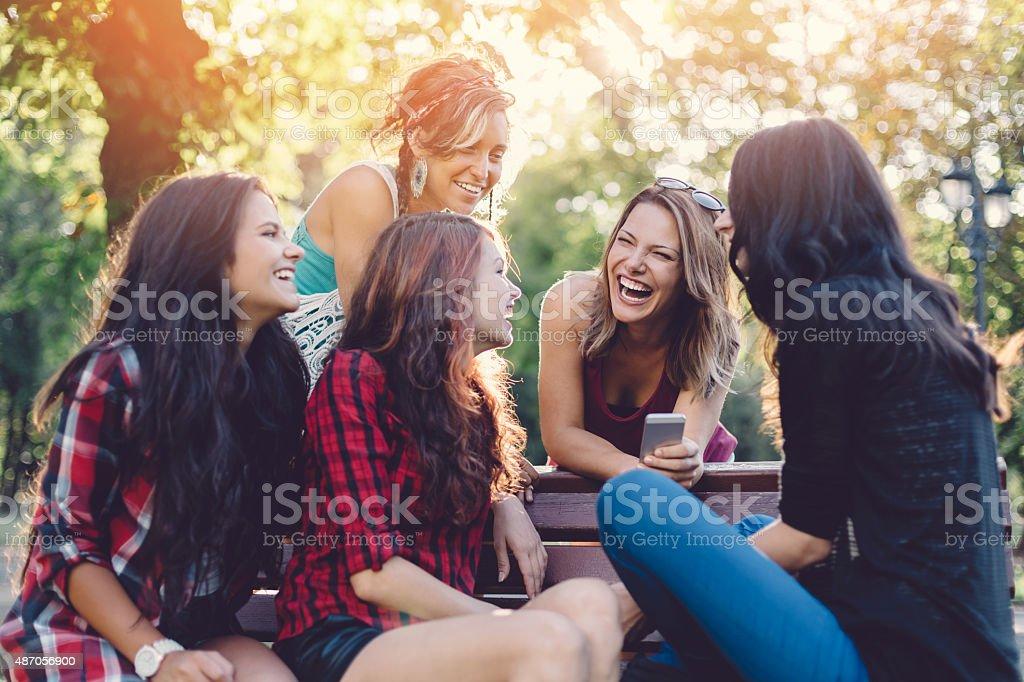 Teenage girls having fun in  the park stock photo