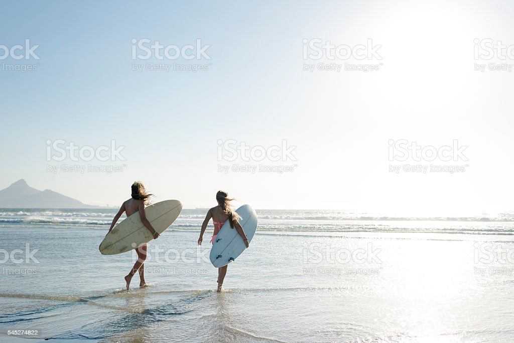 Teenage Girls Heading Out To Surf stock photo