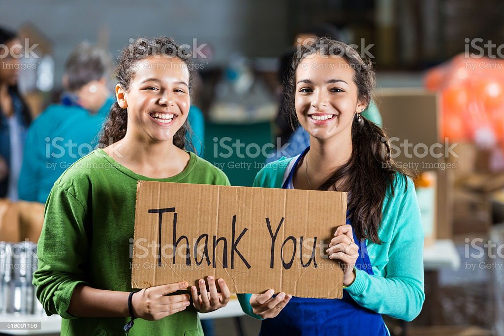 Teenage girls hold 'thank you' sign in food bank stock photo