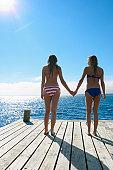 Teenage girls holding hands on pier