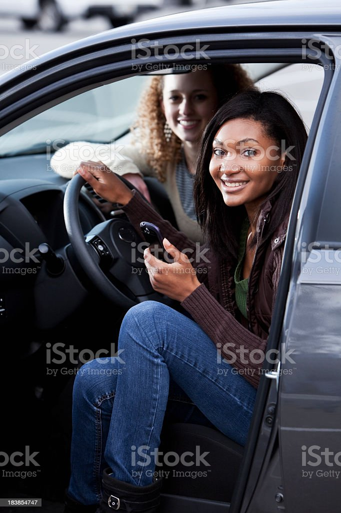 Teenage girls in parked car with mobile phone stock photo
