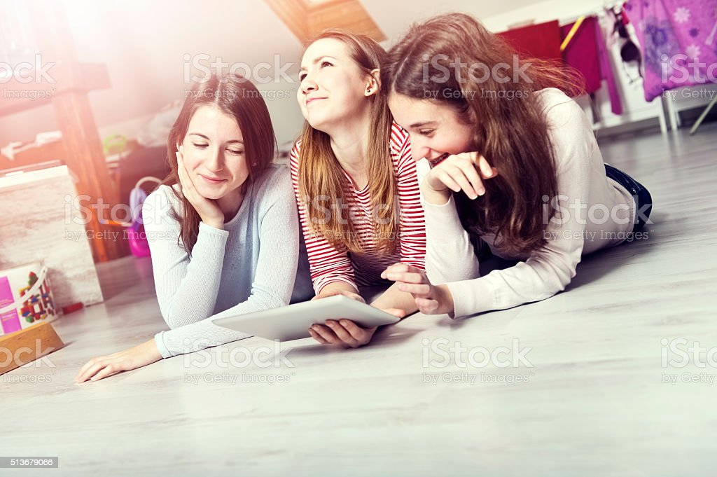 Teenage girls listening to music on a digital tablet. stock photo