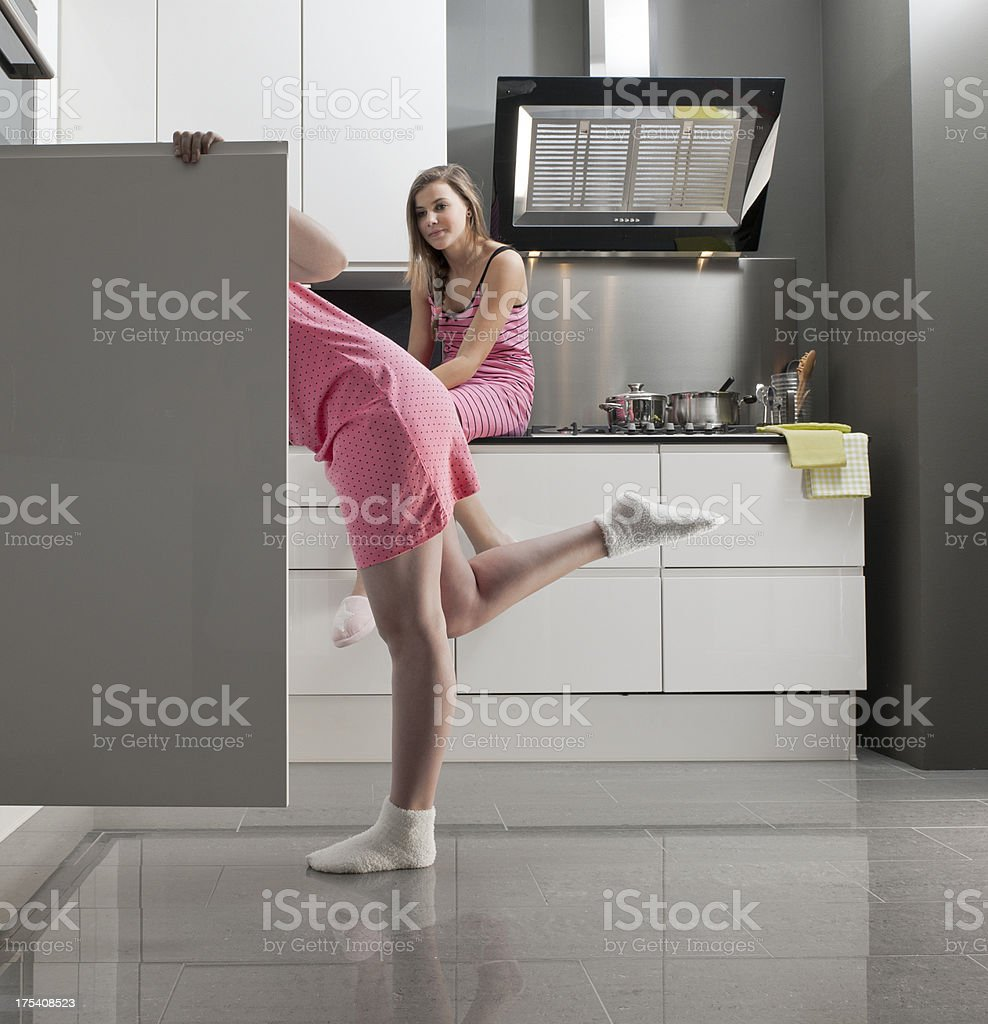 teenage girls looking in refrigerator for midnight snack stock photo