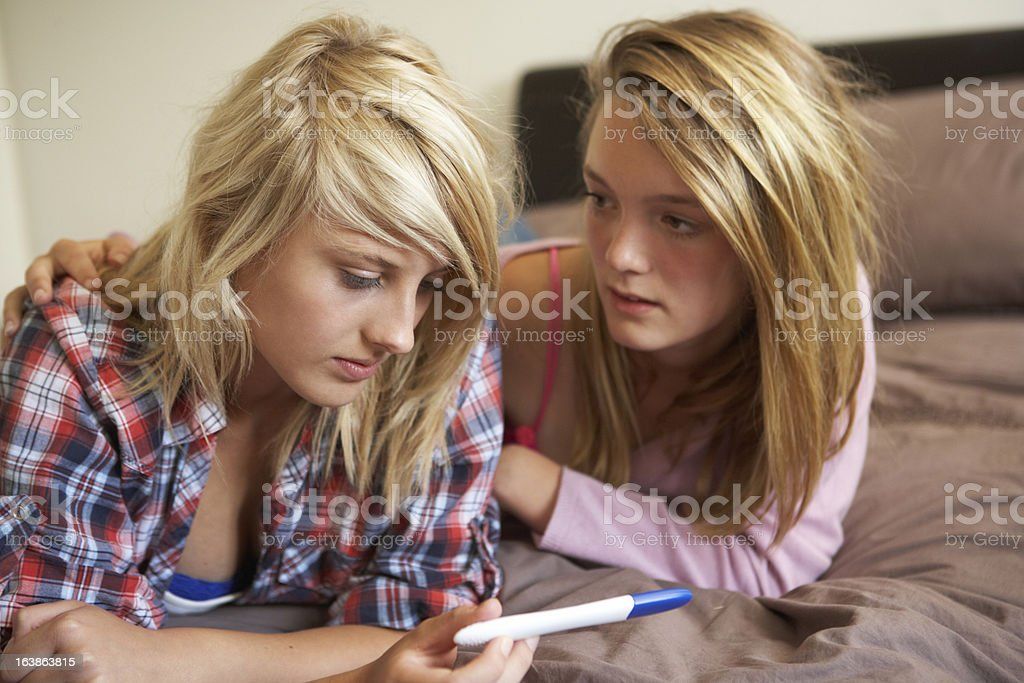 Teenage Girls Lying On Bed Looking At Pregnancy Testing Kit stock photo