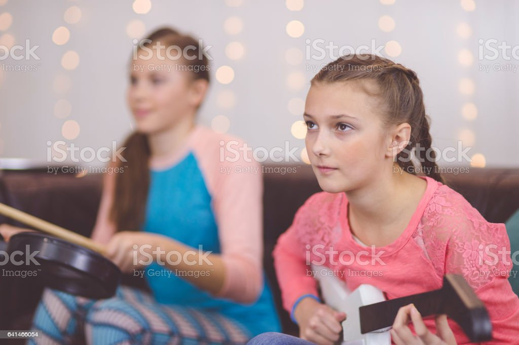 Teenage girls making music together with virtual instruments stock photo