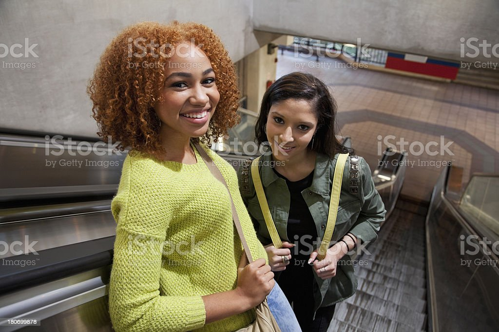 Teenage girls on escalator stock photo
