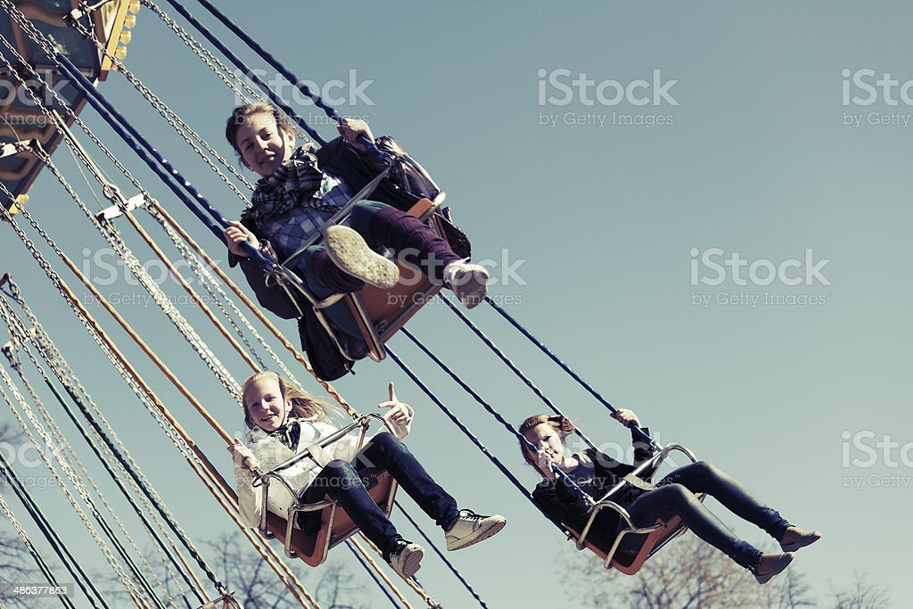 Teenage girls on the chain swing carousel stock photo