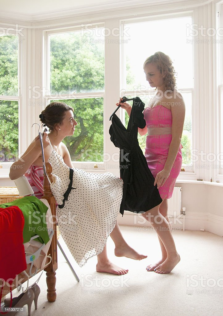 Teenage girls picking out dresses stock photo