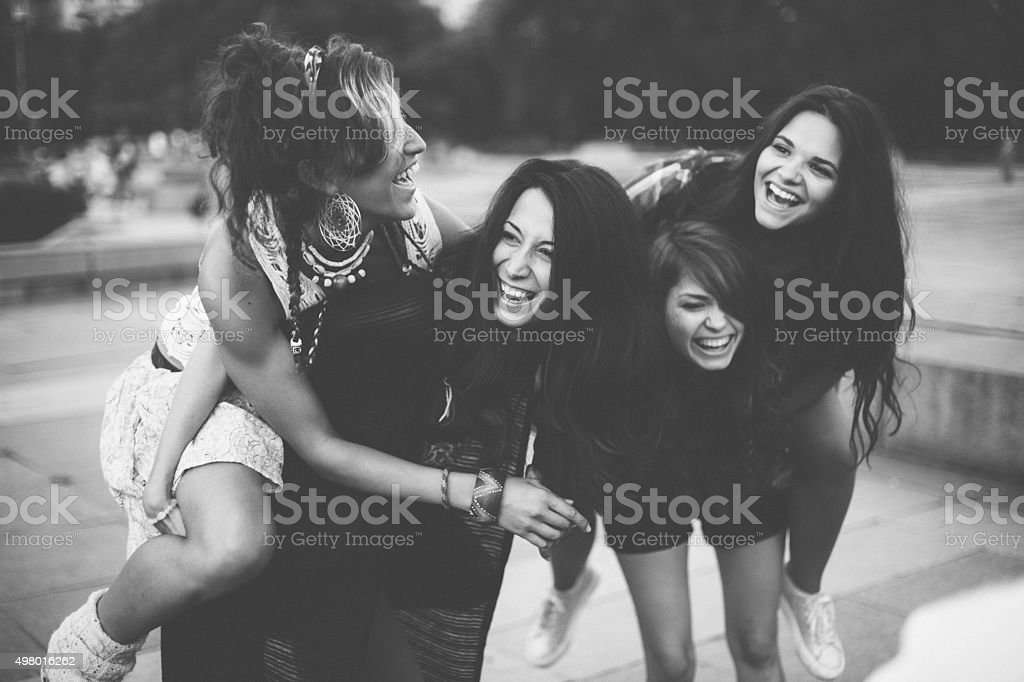 Teenage girls piggyback outside stock photo