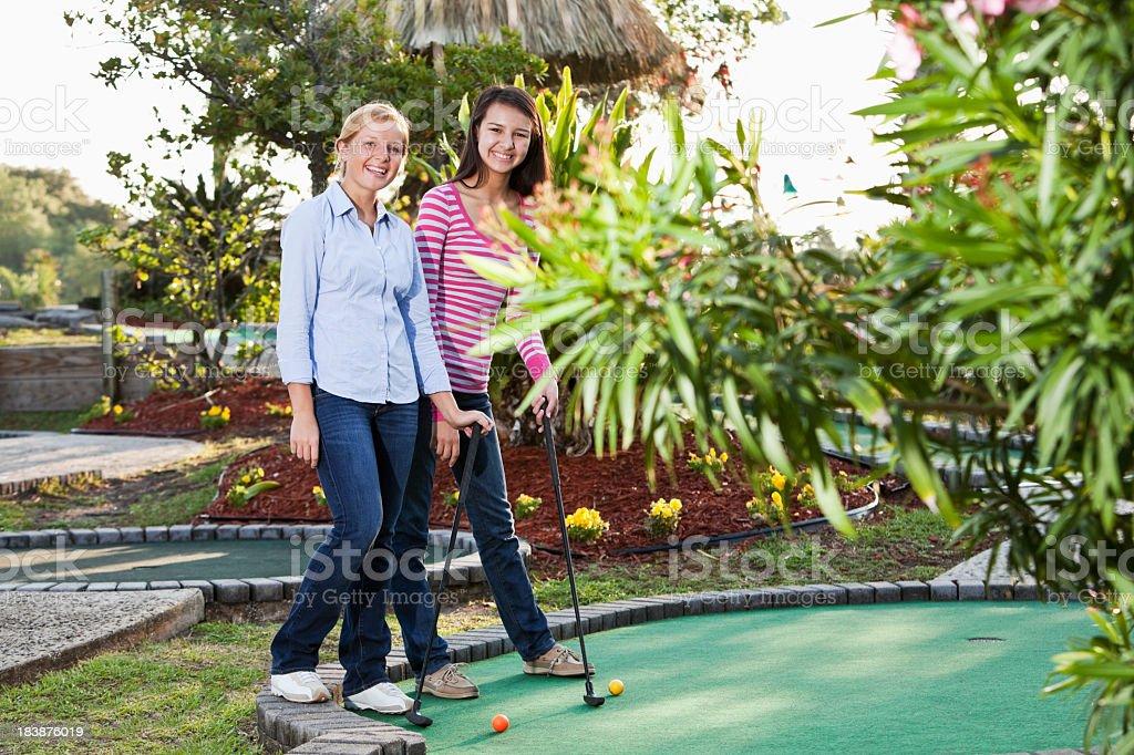Teenage girls playing miniature golf stock photo