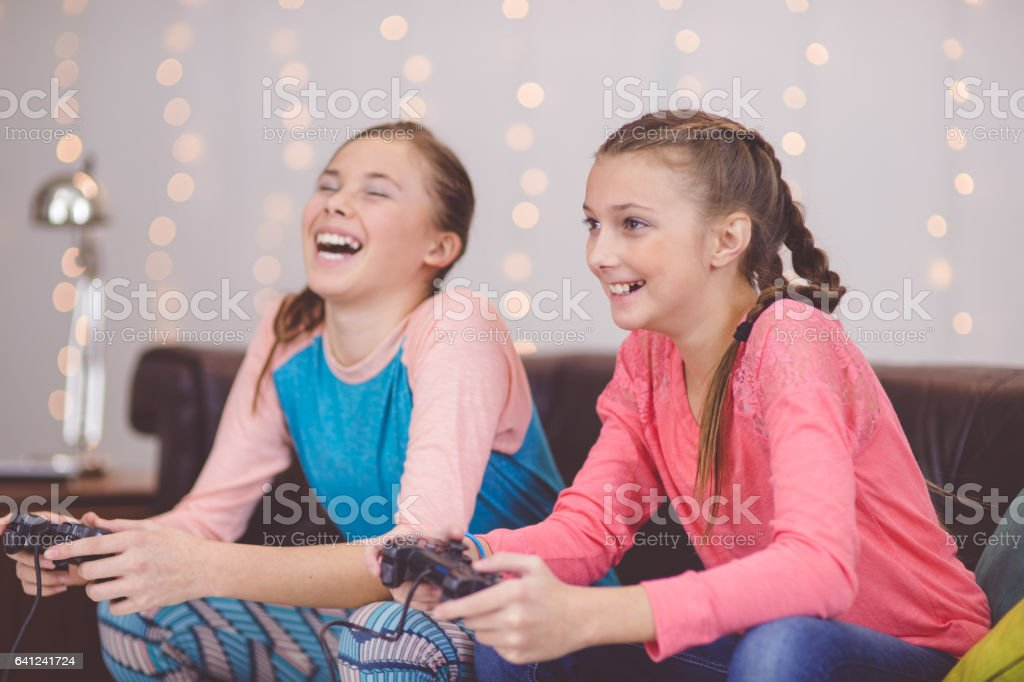 Teenage girls playing video game on couch together and laughing stock photo