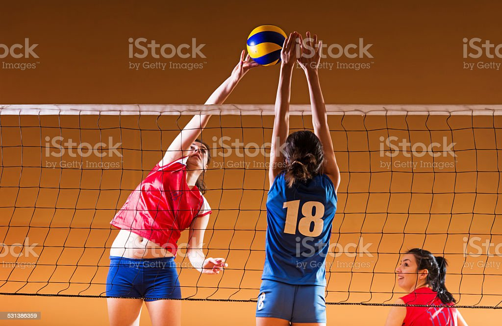 Teenage girls playing volleyball. stock photo