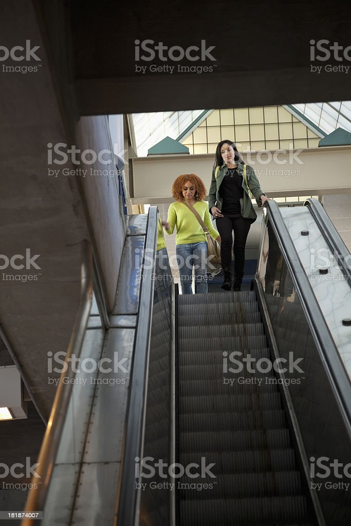 Teenage girls riding down escalator stock photo