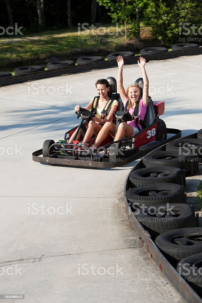 Teenage girls riding go-carts stock photo