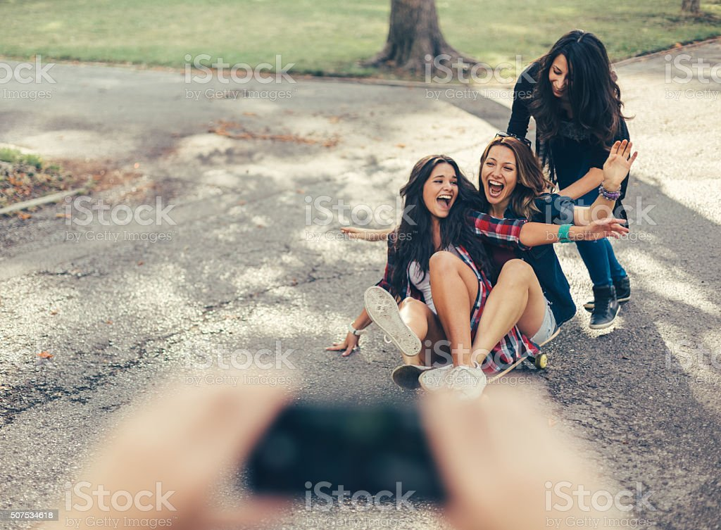 Teenage girls roar with laughter on a skateboard stock photo