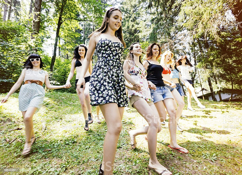 Teenage girls running down forest hill royalty-free stock photo