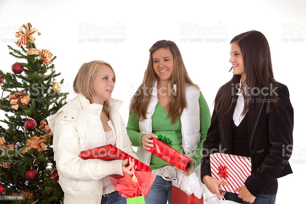 Teenage girls shopping for Christmas carrying gifts royalty-free stock photo
