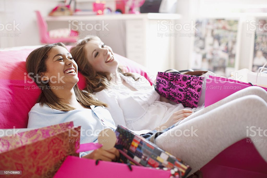 Teenage girls sitting on floor with shopping bags royalty-free stock photo
