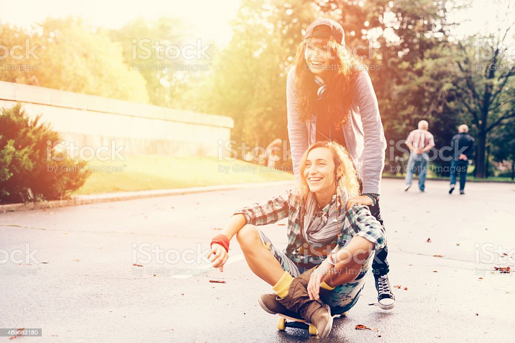 Teenage girls skateboarding in the city park stock photo