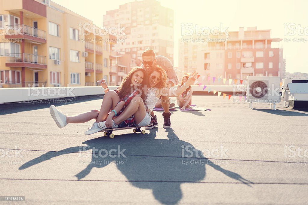 Teenage girls skateboarding on the rooftop stock photo