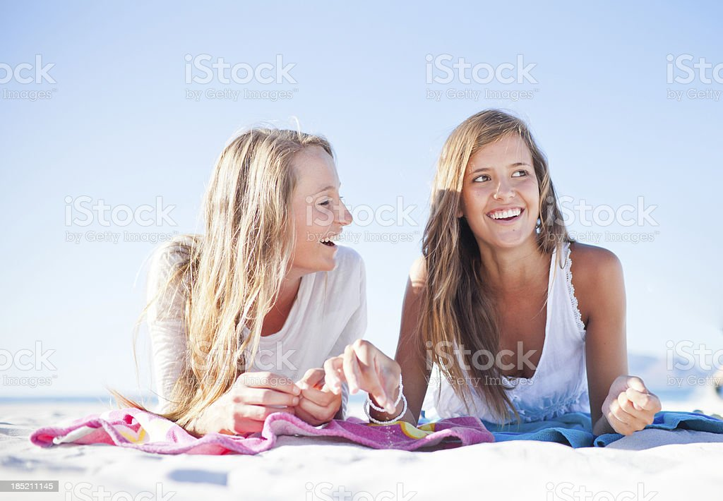 Teenage girls smiling as they check out the surfer boys stock photo